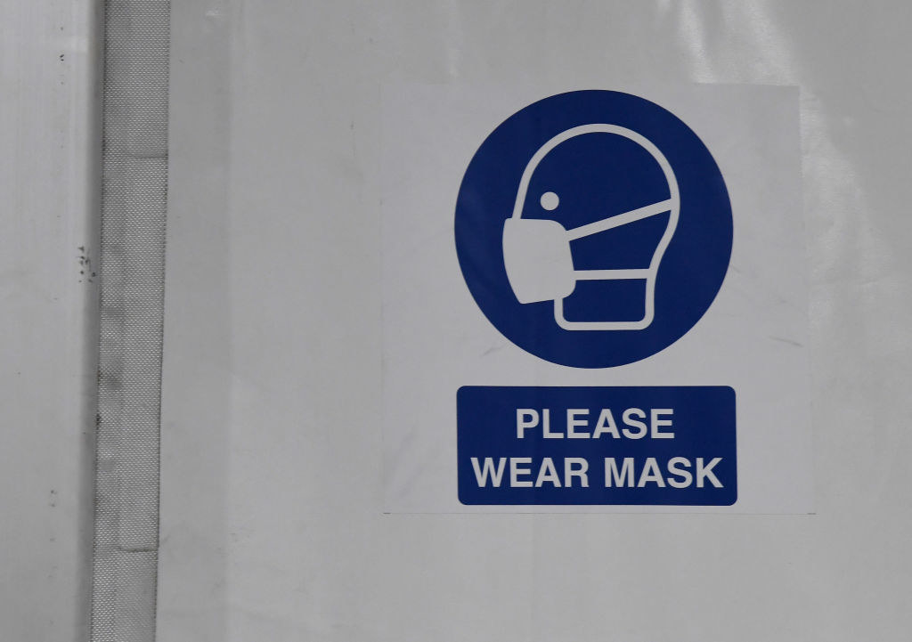 A poster that says 'Please wear a mask'