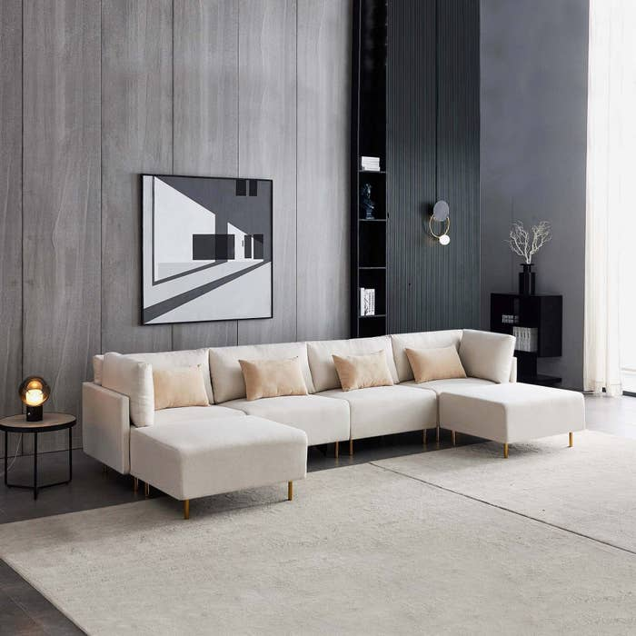beige sectional with two removable ottomans and several decorative pillows
