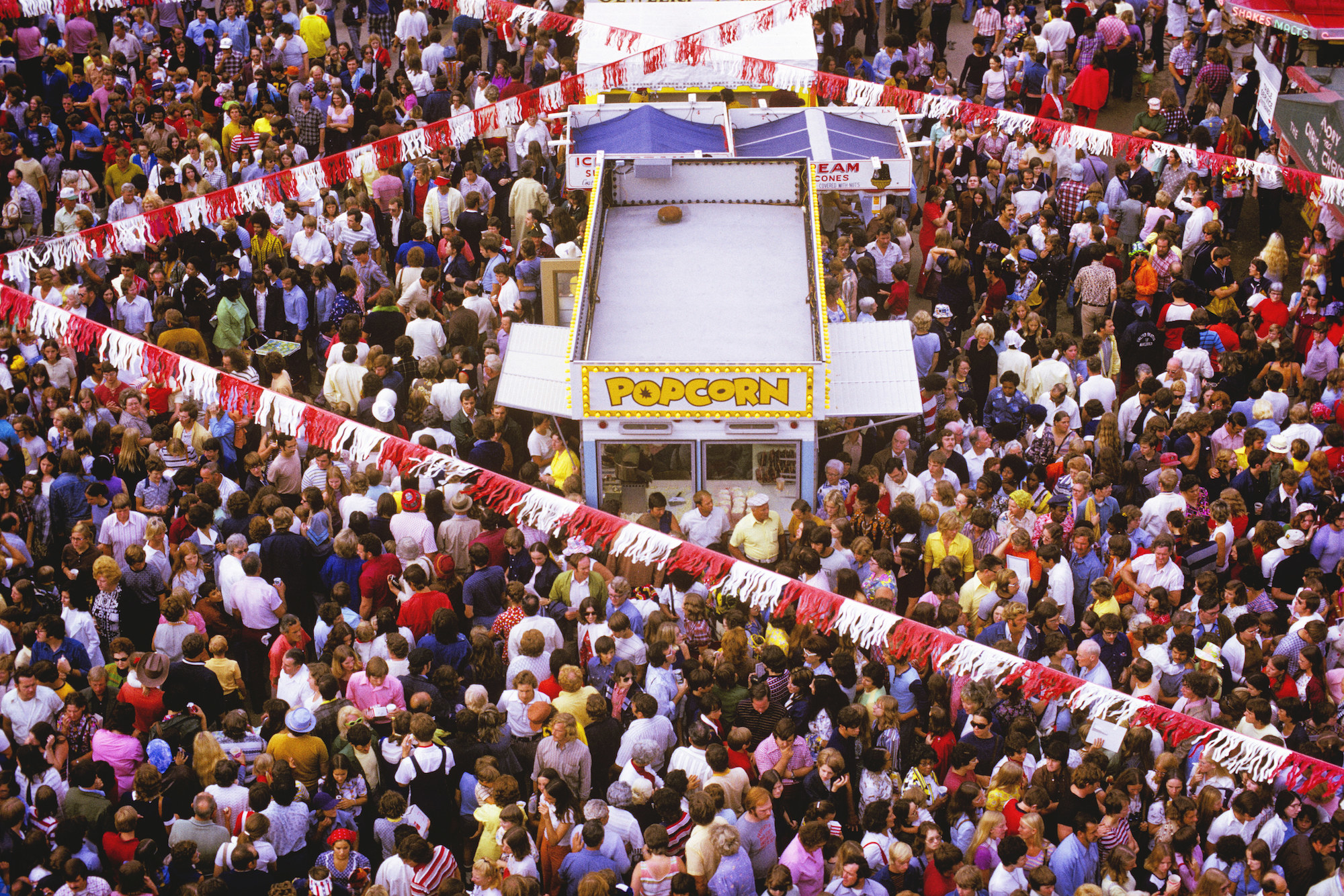 A large crowd of people attends a fair