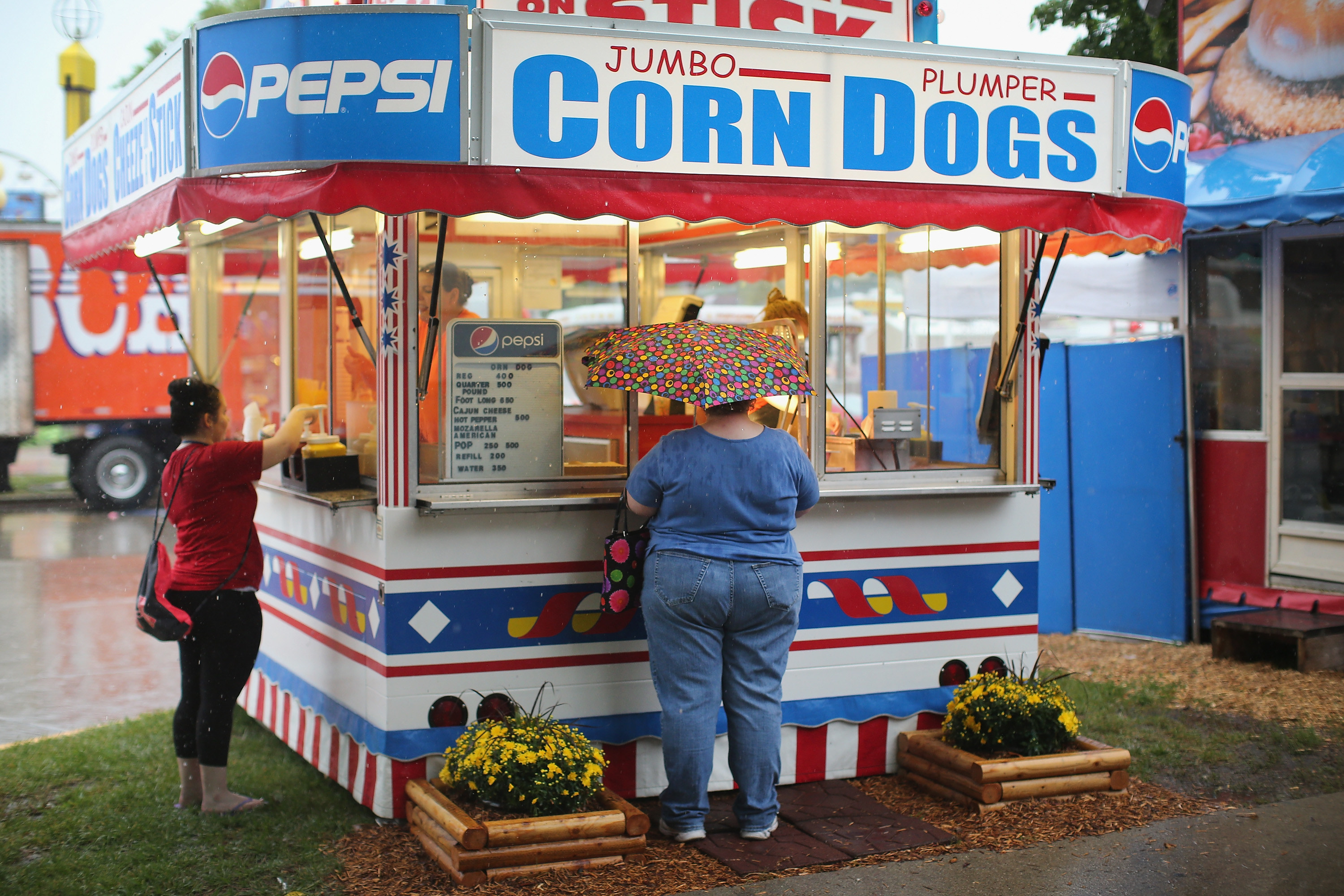 Fair attendees order food at a corndog stand on a rainy day at the Iowa State Fair
