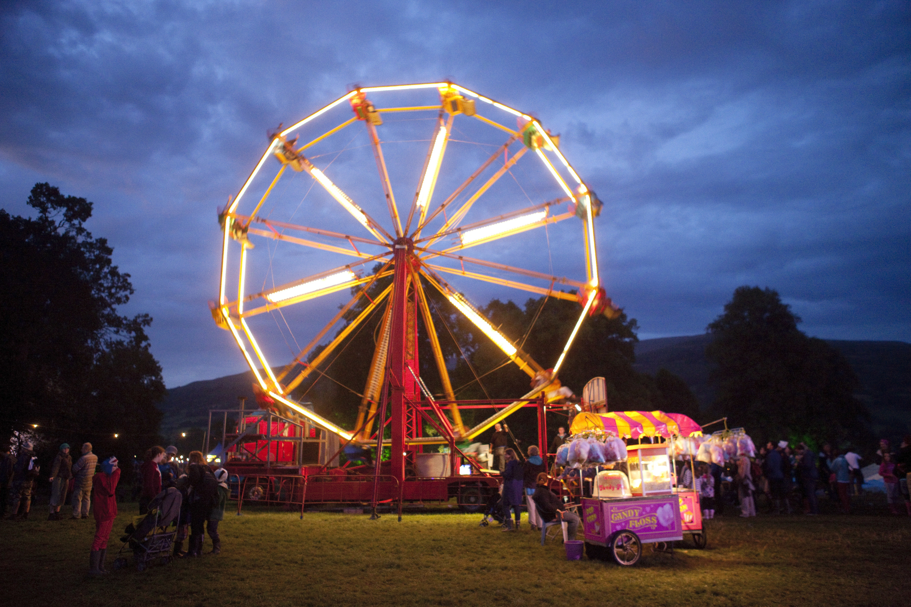 A ferris wheel and cotton candy stand light up the evening sky at the Green Man Festival