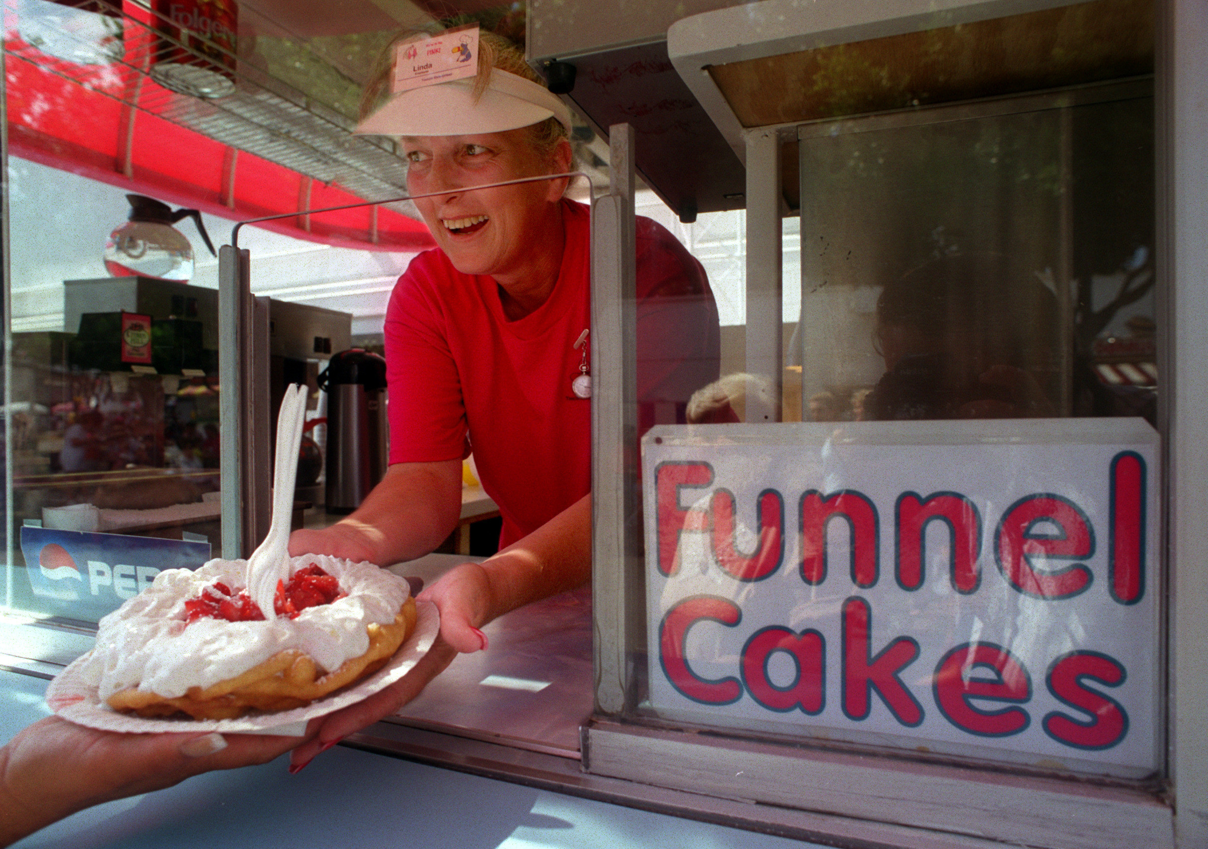 A female worker at a funnel cake stand passes a guest a cake