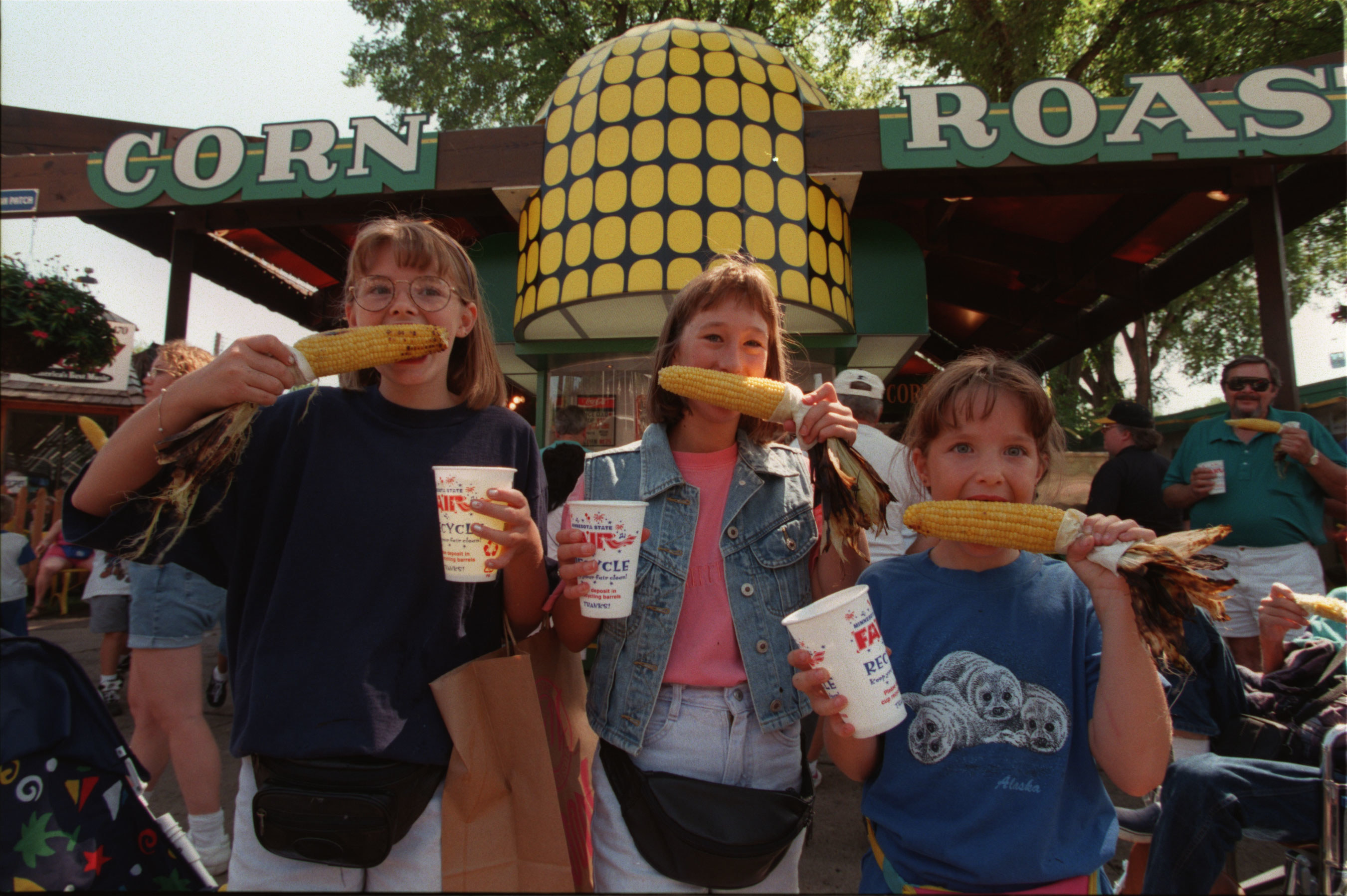 Three young females hold up corn on the cob and hold cups at the state fair