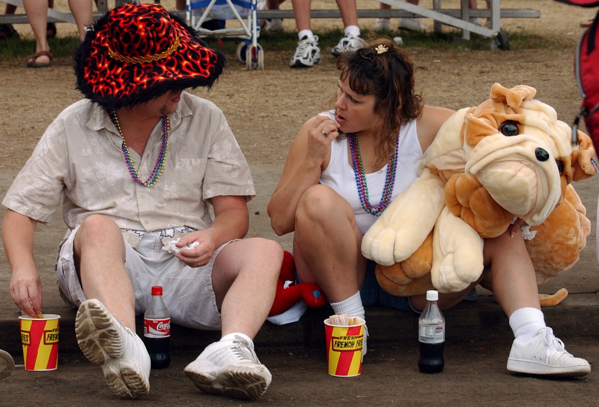 Two people eat popcorn and sit on a curb with prizes from the Minnesota State Fair
