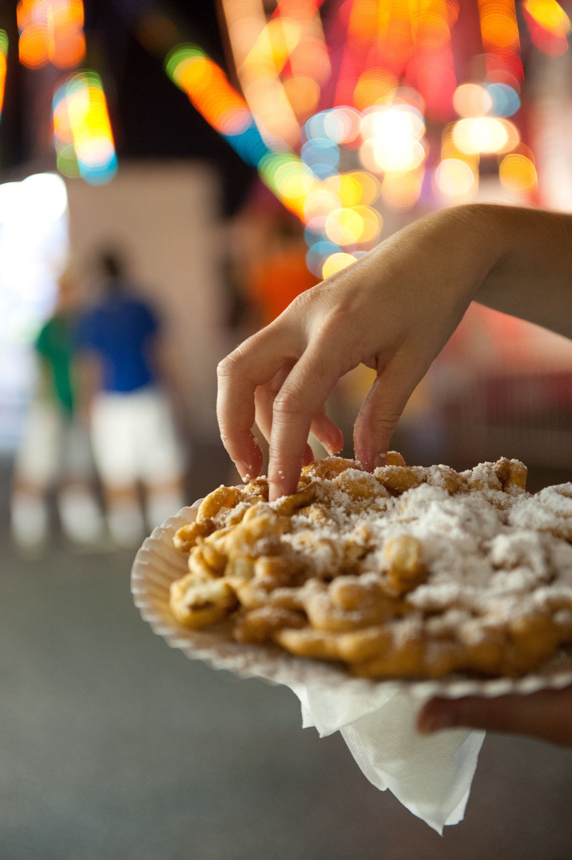 A person holds a sugar topped funnel cake in hand at the Maryland State Fair