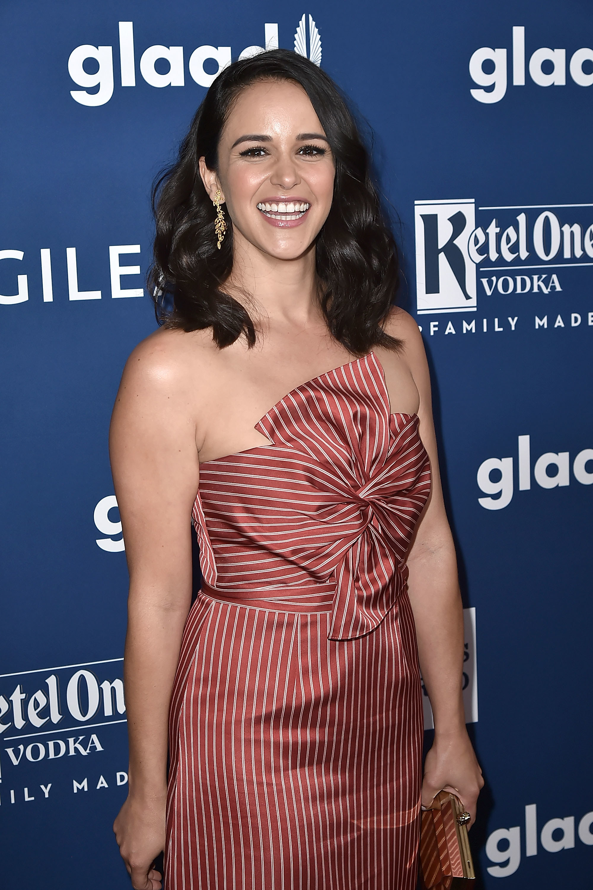 Melissa smiling at a red carpet event and wearing a striped strapless dress