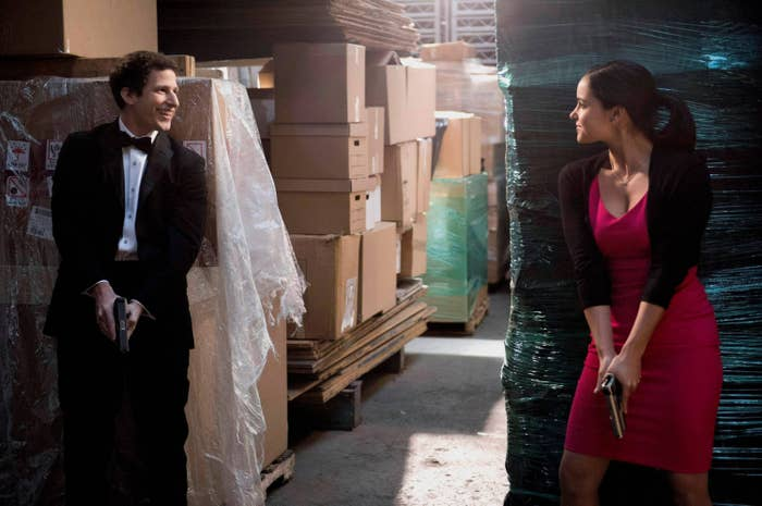 Jake and Amy dressed up with guns drawn in a warehouse