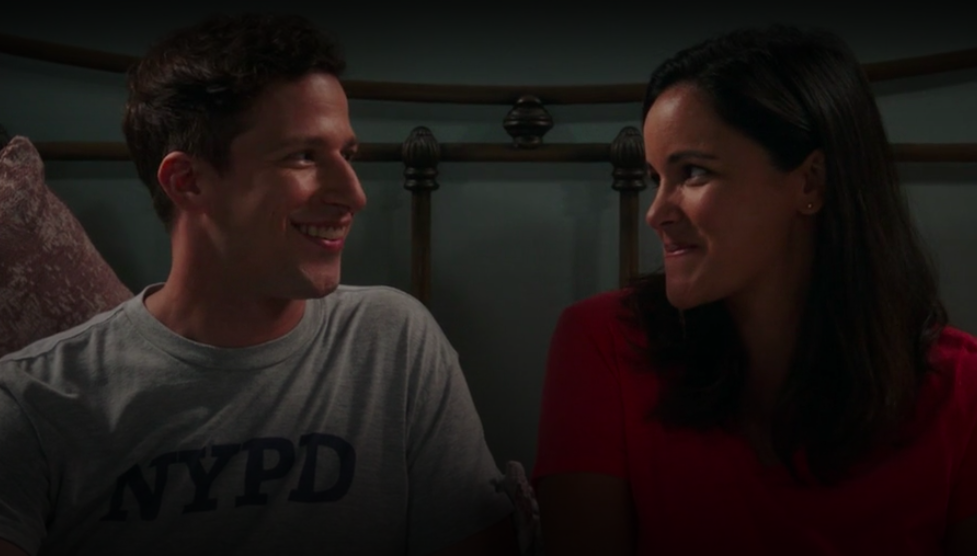 Jake and Amy smiling at each other while sitting in bed