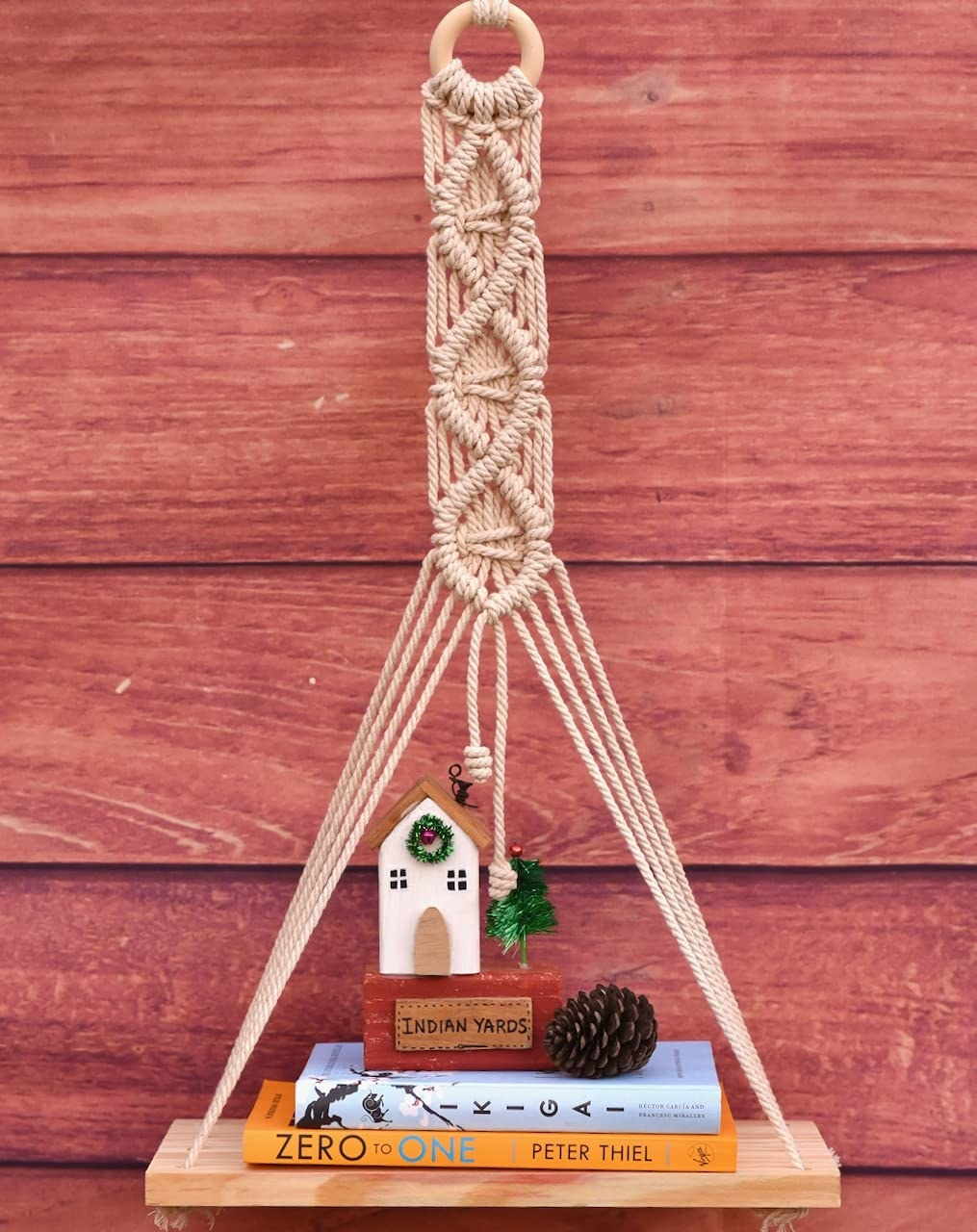 A macrame wall hanging with a wooden shelf holding a few books and showpieces