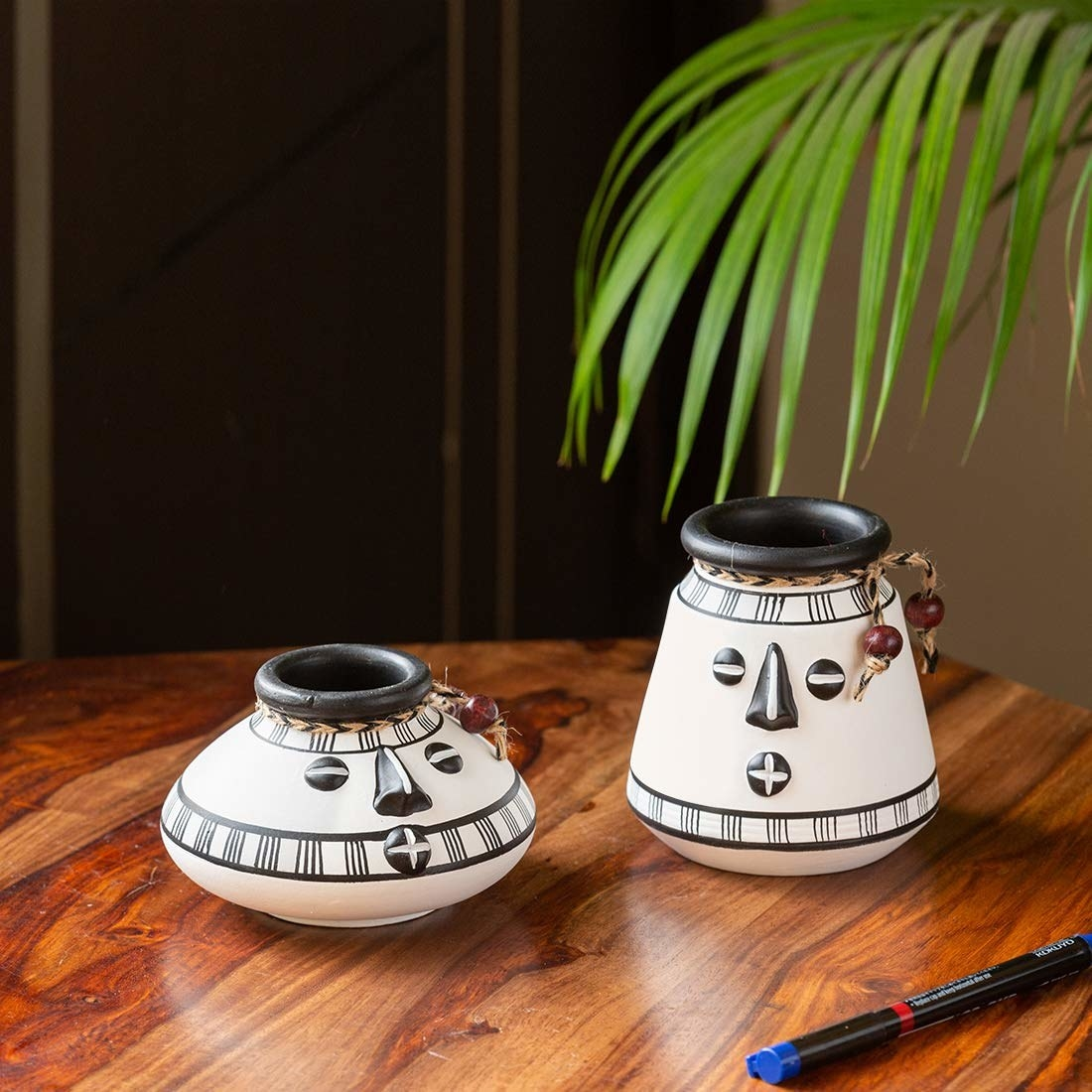 Two different sized pots in black and white with eyes, nose and mouth painted on it