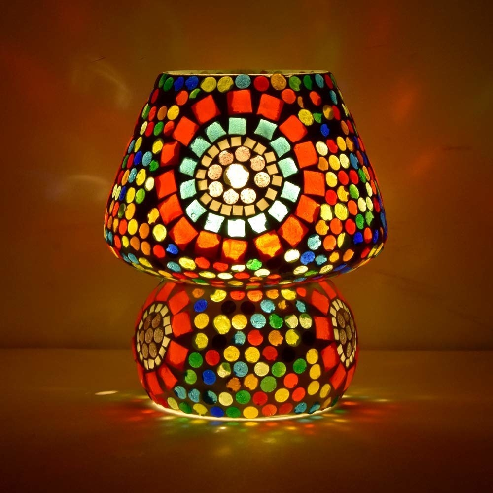 A mosaic lamp decorated with coloured glass pieces lit up in a dark room