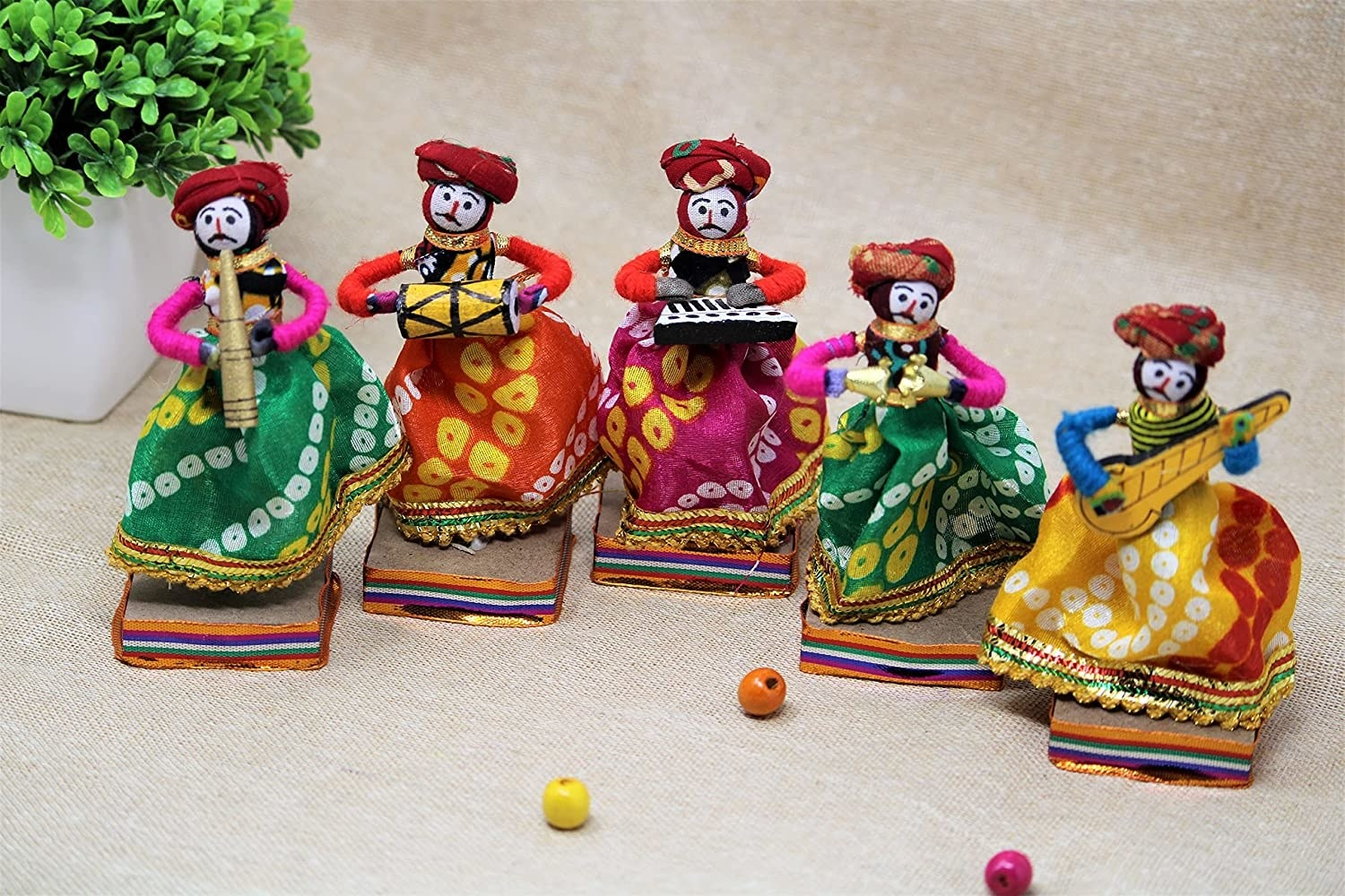 A set of 5 Rajasthani puppets each holding a musical instrument and wearing turbans and local Rajasthani attire