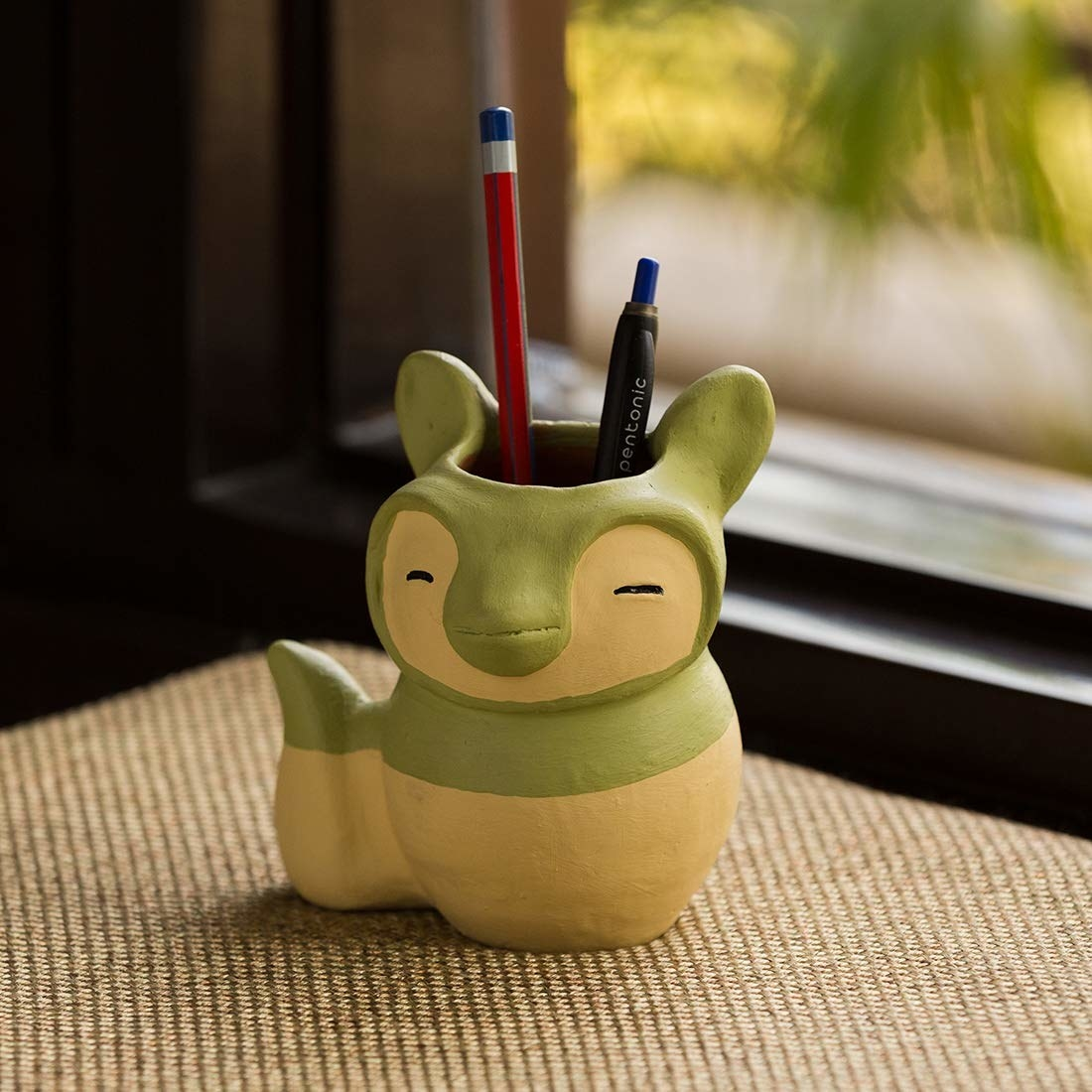 A cat-shaped pen stand in white and green