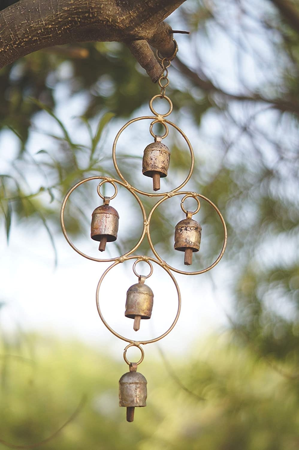 A metal wind chime in a brass colour with 5 metal bells adorned on the geometric design