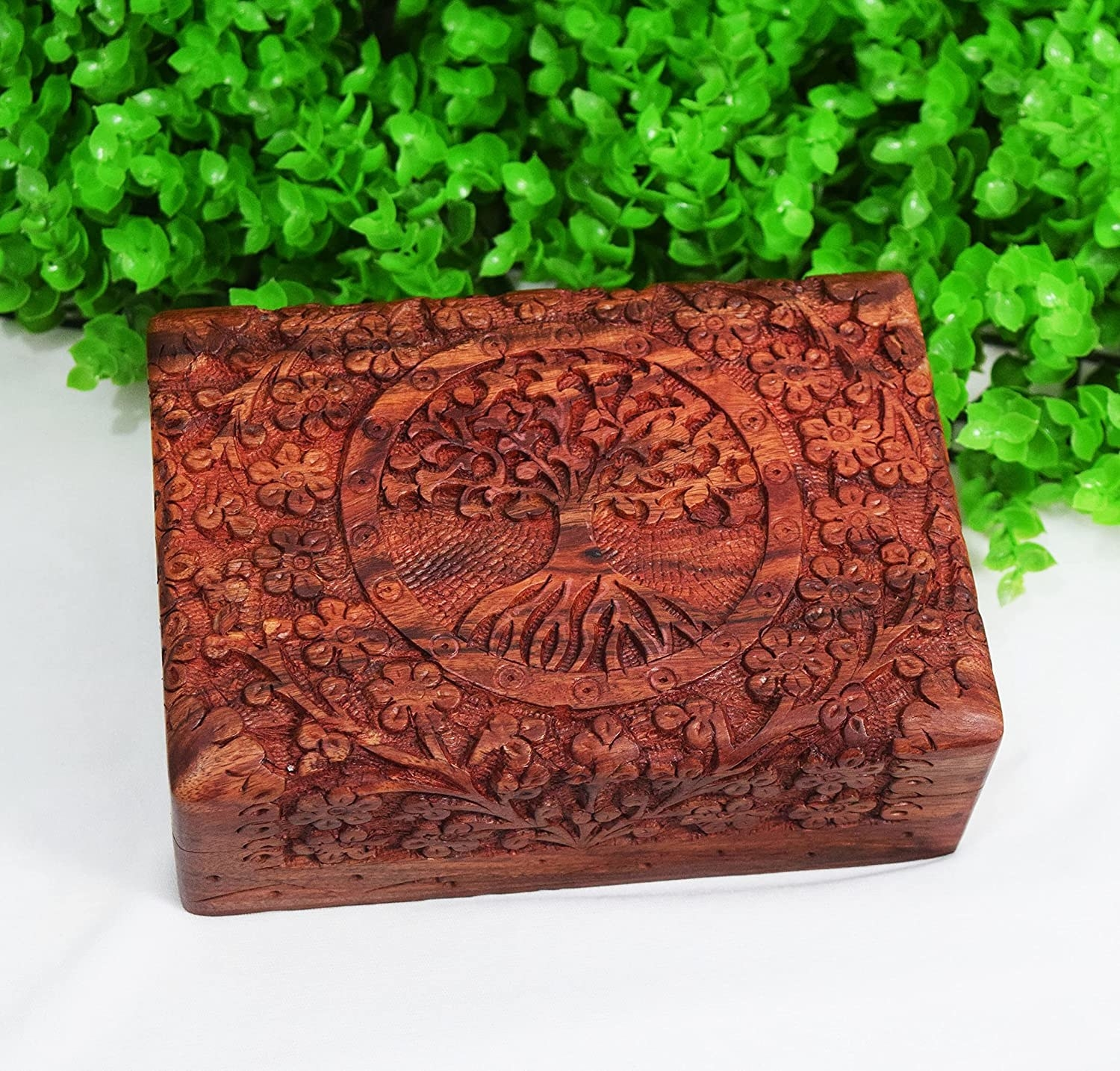 A wooden carved jewellery box with detailed carvings on the body