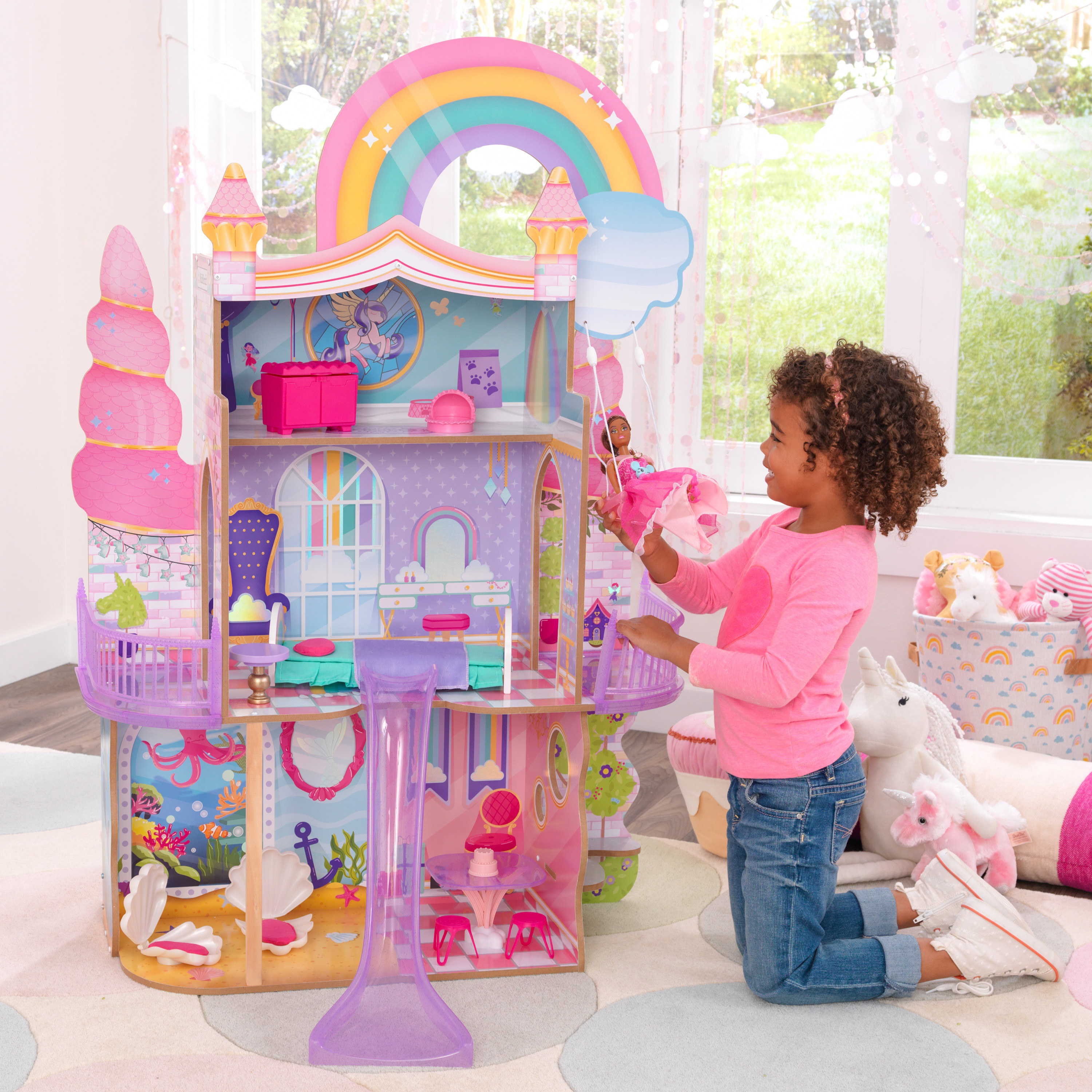 A model playing with the rainbow unicorn mermaid wooden dollhouse