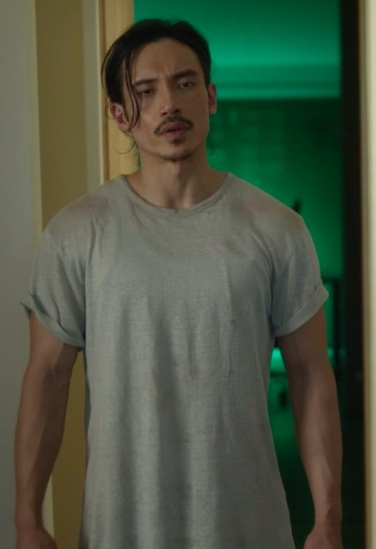 A disheveled Yao wears a dirty grey t-shirt and stadns in a doorway