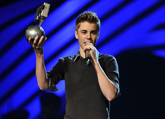Justin Bieber holding his Moon Man on stage at the 2011 MTV VMAs