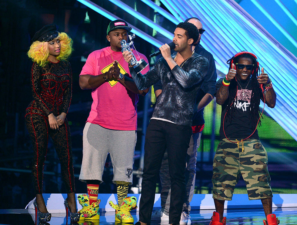 Drake with a crowd of people behind him giving an acceptance speech at the 2012MTV VMAs