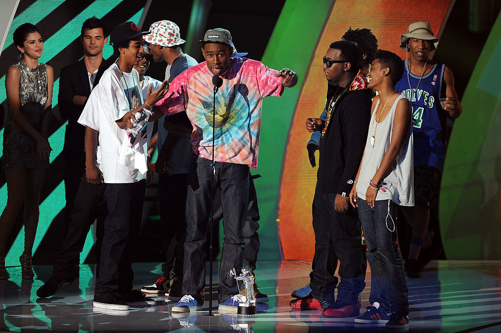 Tyler, The Creator on stage with a crowd of people talking into the mic at the 2011 MTV VMAs