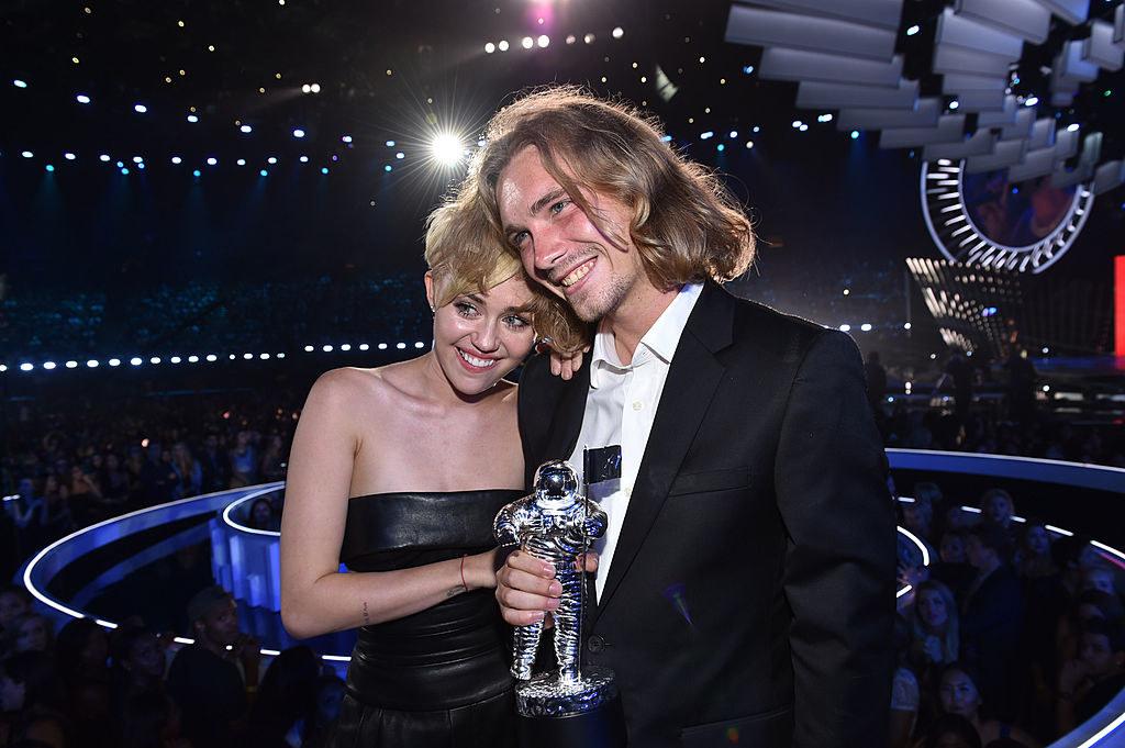 Miley Cyrus posing with a man holding her Moon Man award at the 2014MTV VMAs