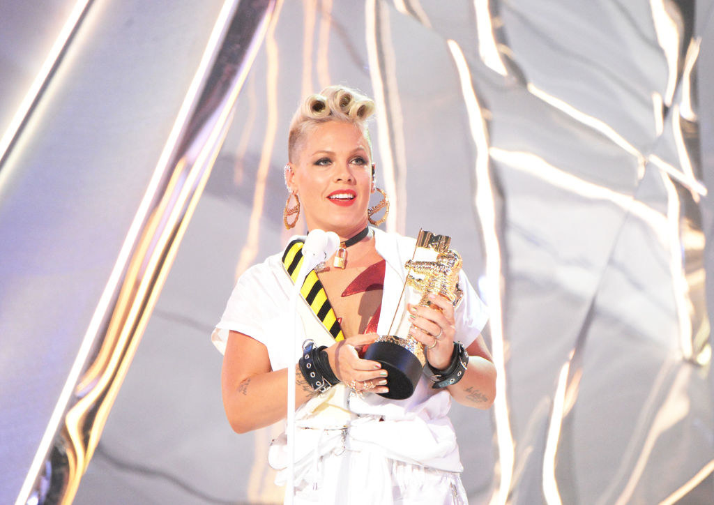 Pink on stage at the mic giving a speech holding her Moon Man at the 2017MTV VMAs