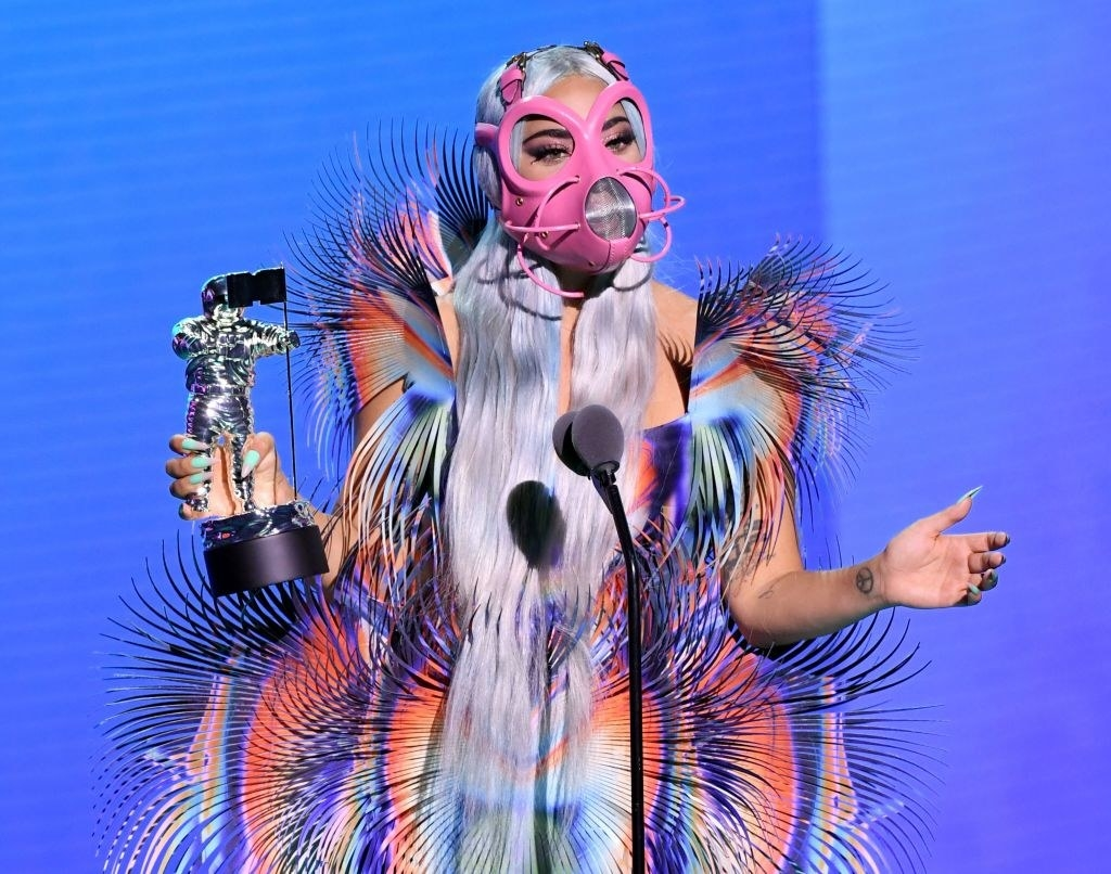 Lady Gaga at the mic wearing a bright costume giving her acceptance speech at the 2020MTV VMAs