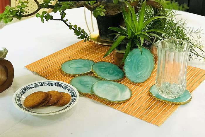 Green with gold-rimmed resin coasters placed on a table with a table mat, a glass and plate of biscuits