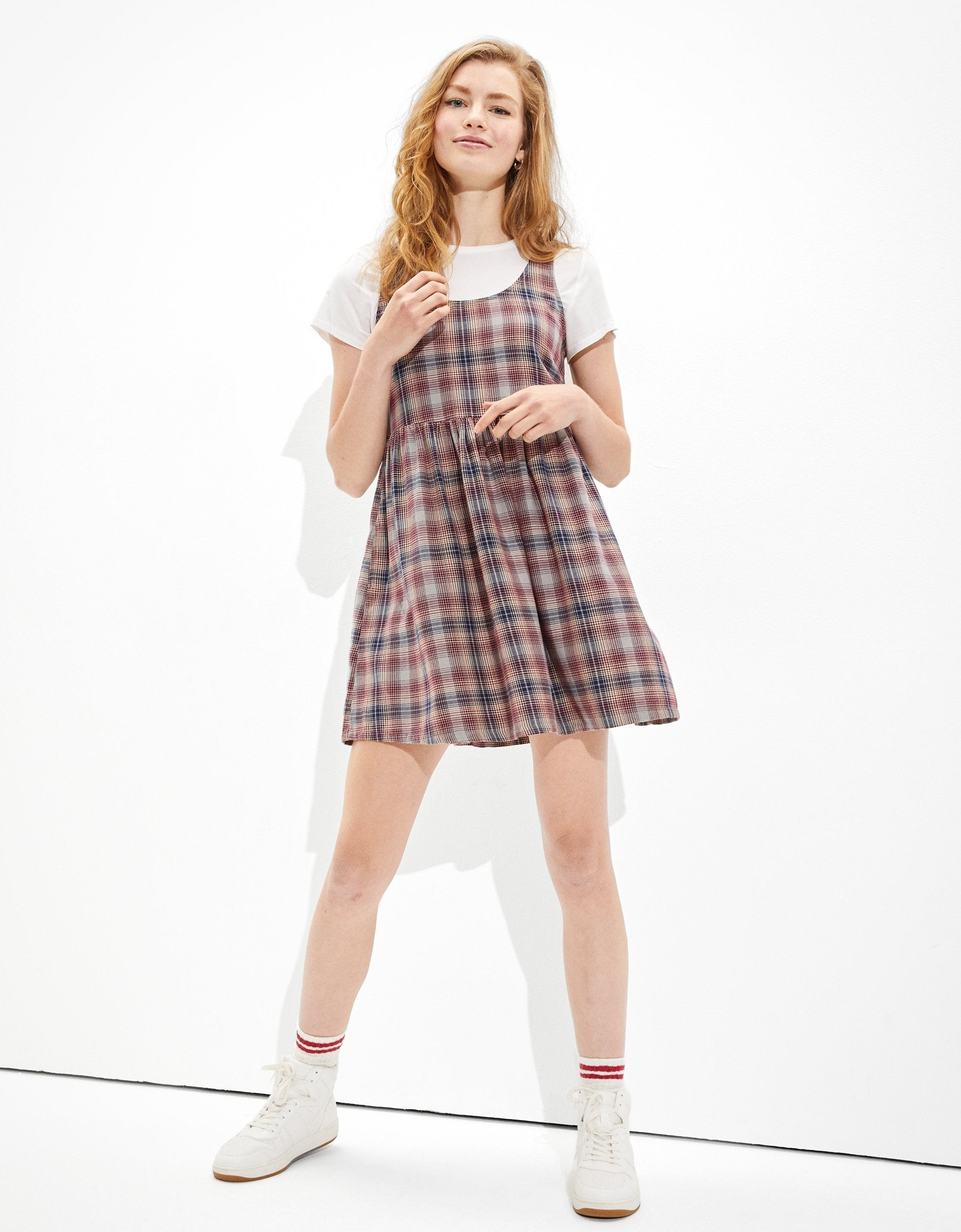 a model wearing a red and black plaid dress over a white tee