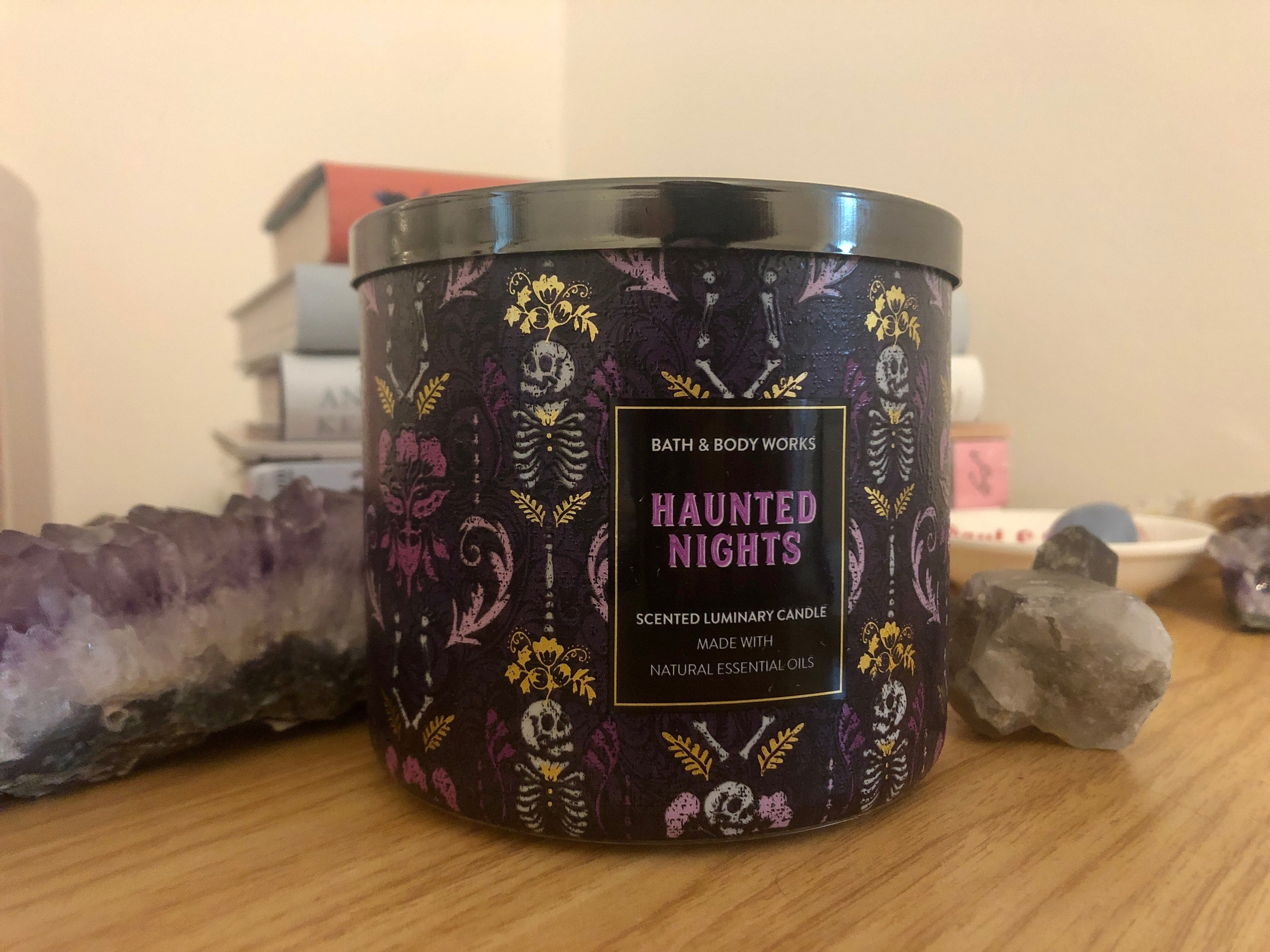 a candle with a purple skeletal design on it