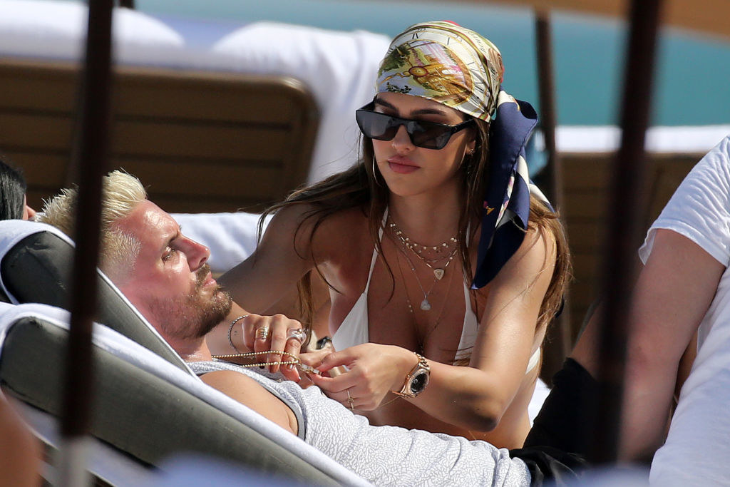 Scott laying on a beach lounge chair with Amelia sitting next to him and adjusting his necklace