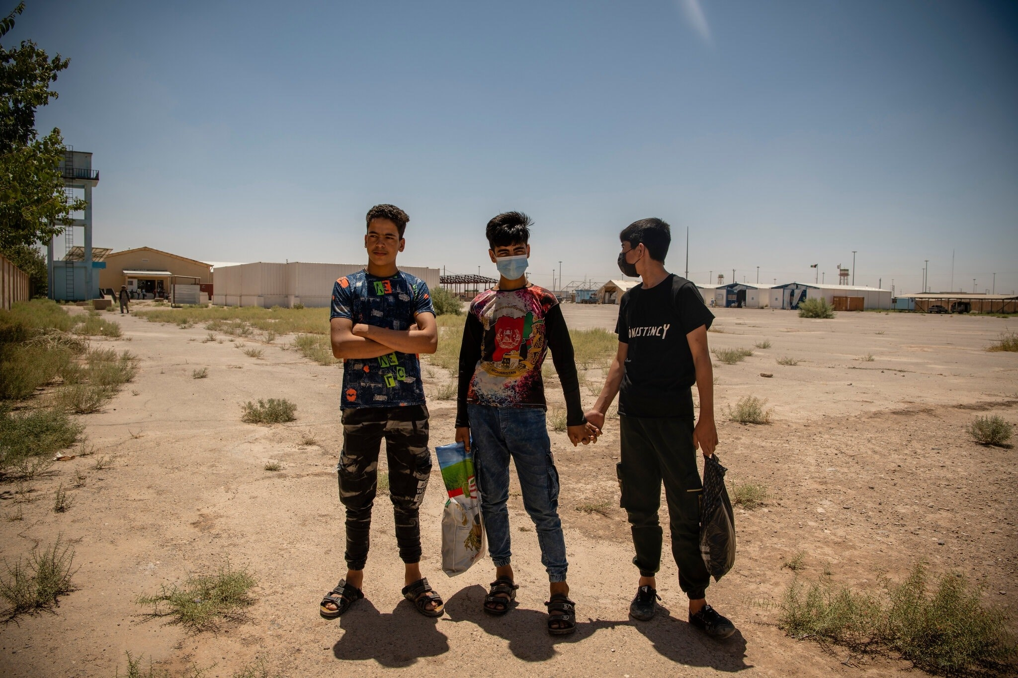 Three young afghan boys stand in front of a desert and a few low buildings, carrying shopping bags