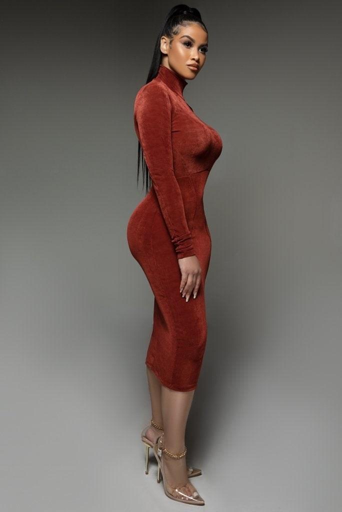 a model in a form fitting high neck burnt orange dress