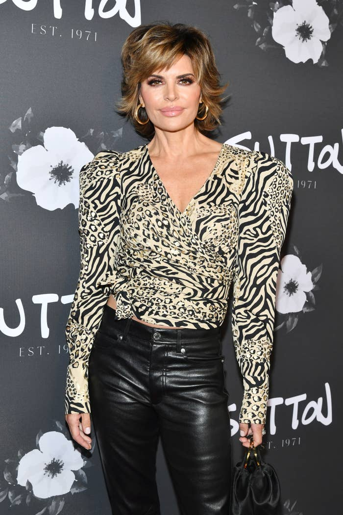 Lisa posing for a photo on a red carpet in an animal-print shirt and leather pants