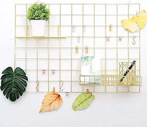 A gold steel grid with dried leaves, stationery, a notebook, potted plant and some wooden clips attached
