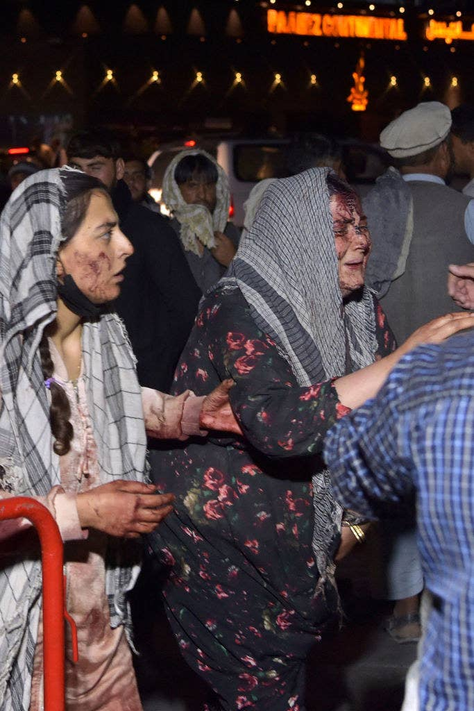 Two women in a crowd have bloody, bruised faces