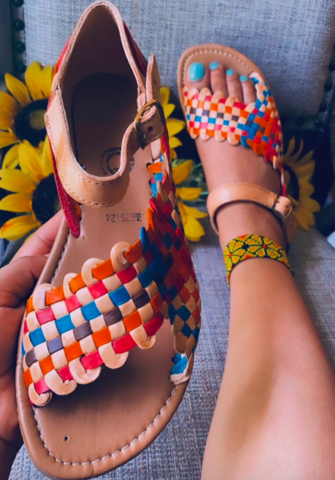 A model wearing aHuarache on one foot and holding the other in their hand, close to the camera