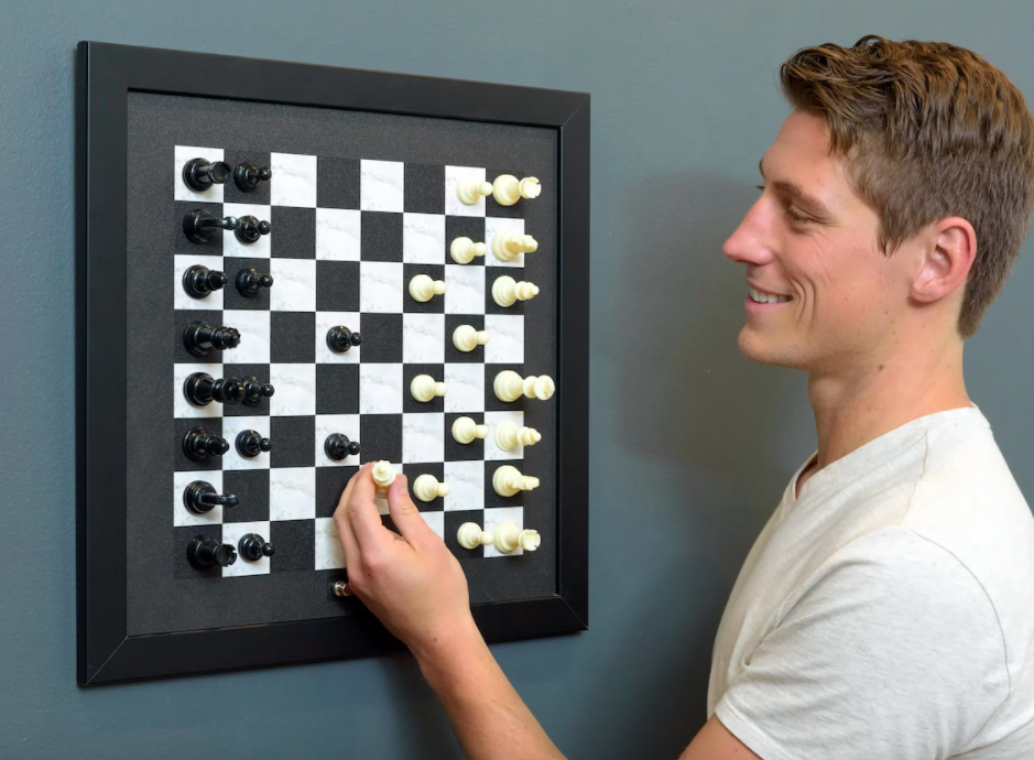 A person playing the magnetic chessboard attached to the wall