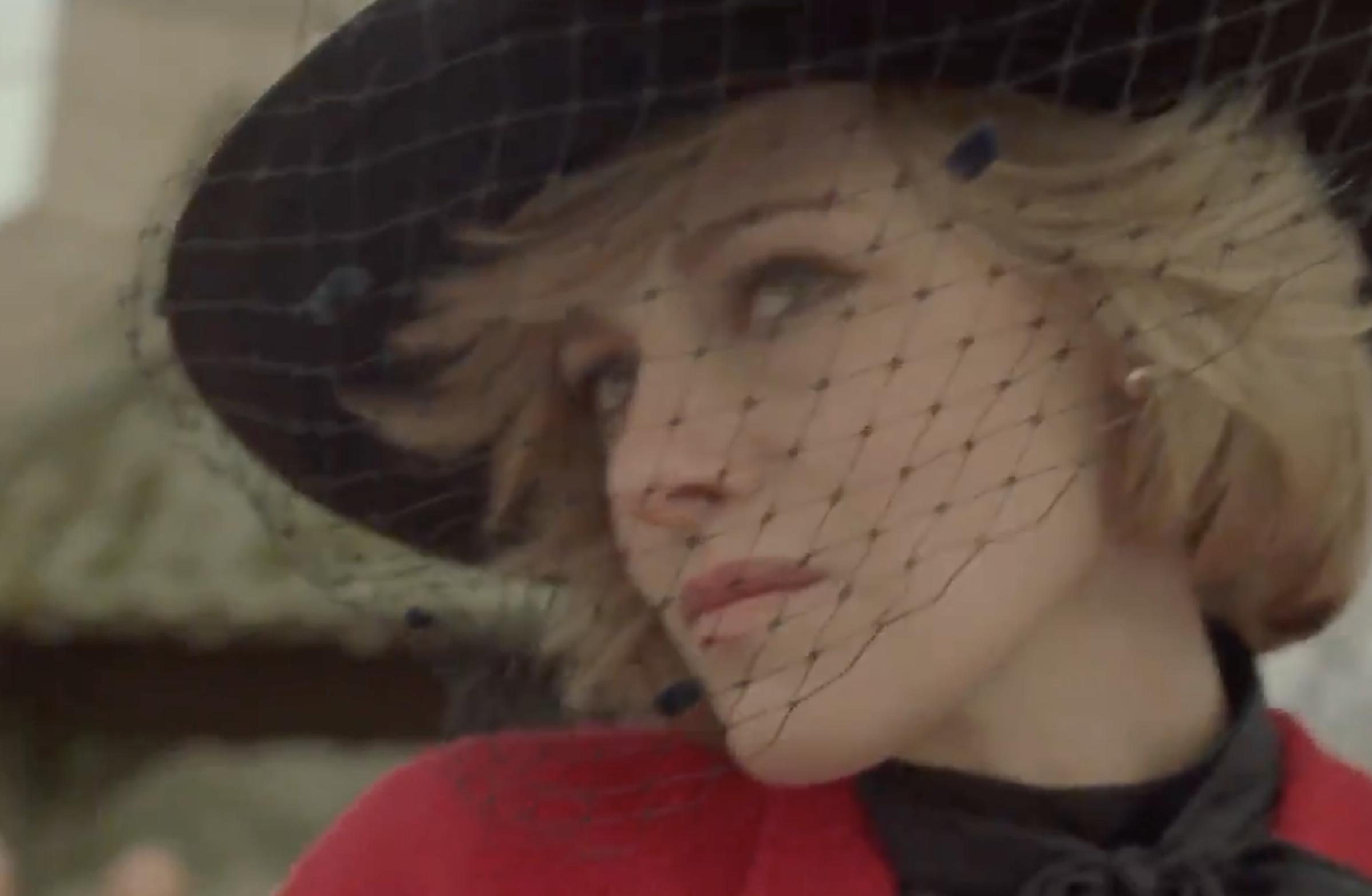Kristen as Diana wearing a wide-brim black hat with birdcage veil