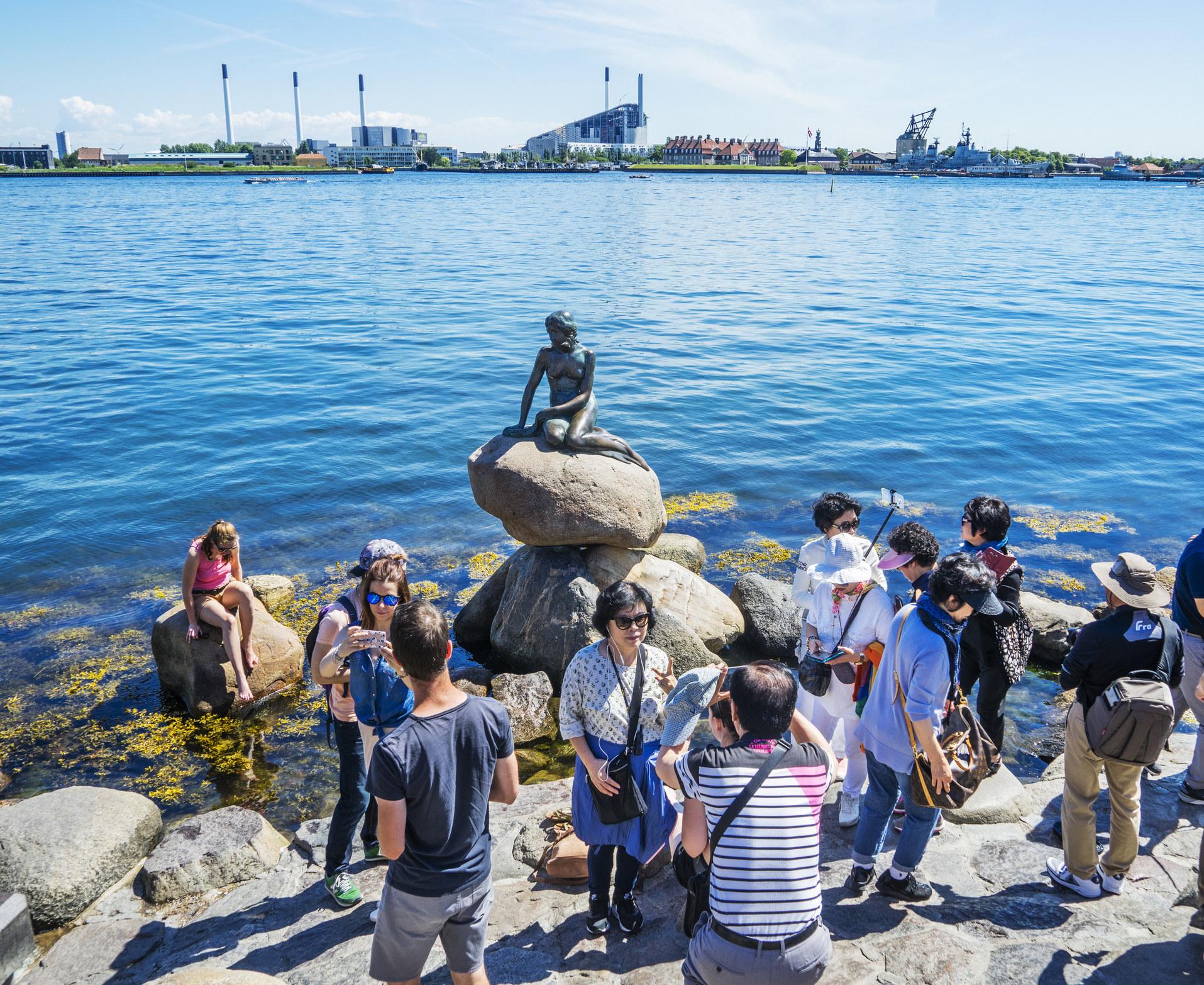 Tourists gathering around the Little Mermaid statue in Copenhagen