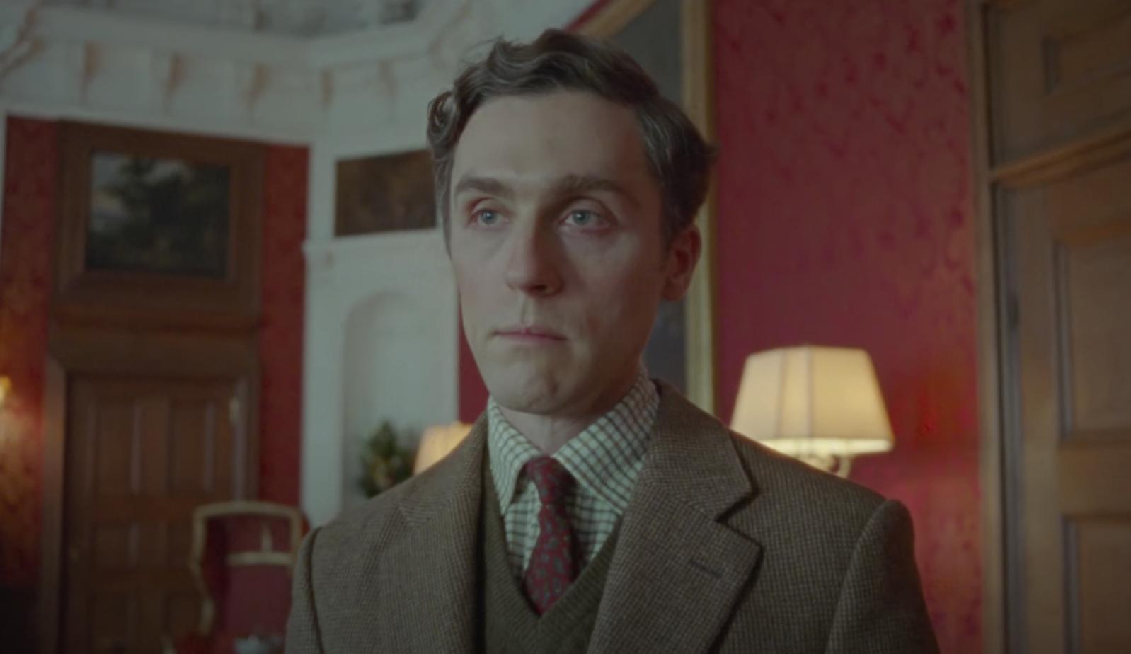 Jack as Charles in a dark suit and tie