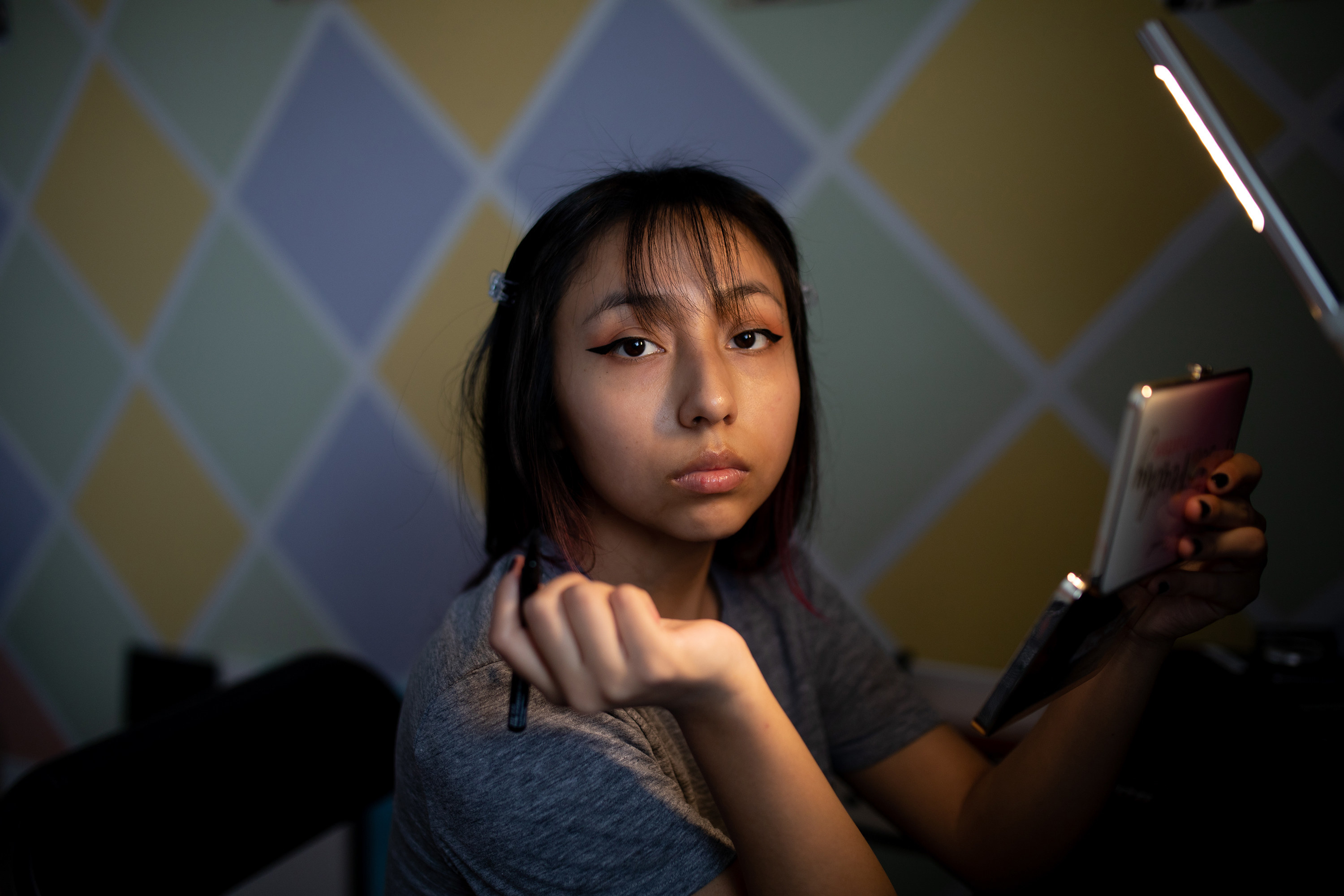 A young girl sits indoors with a tablet and pen, looking at the camera
