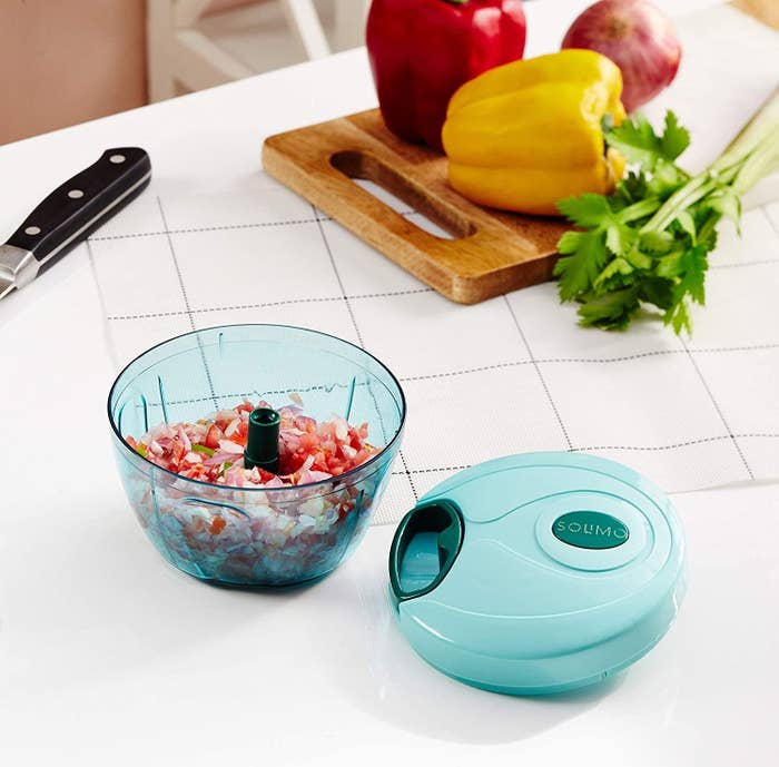 Manual food chopper with chopped onions and tomatoes in it