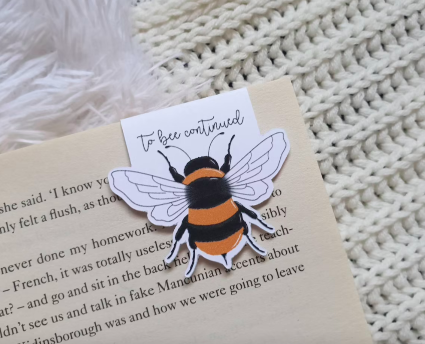 """TheBee Magnetic Bookmark, that reads """"to bee continued"""" placed inside a book"""