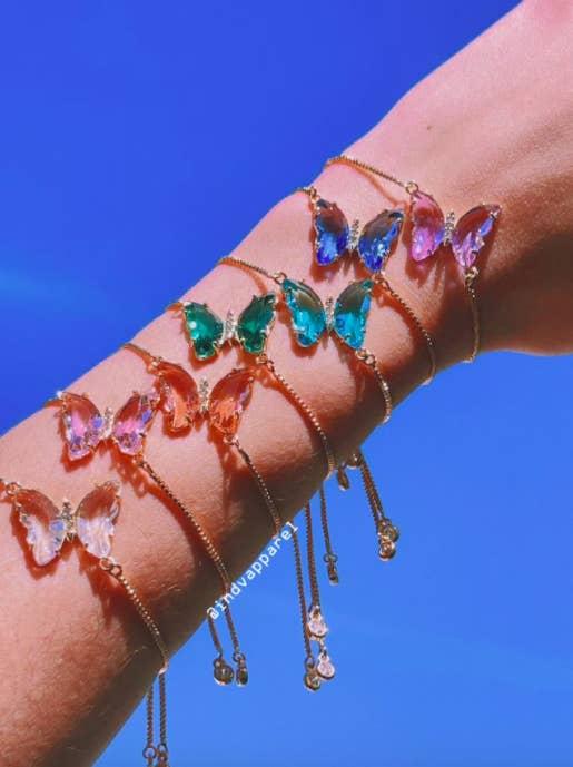 A models hand wearing six of the bracelets