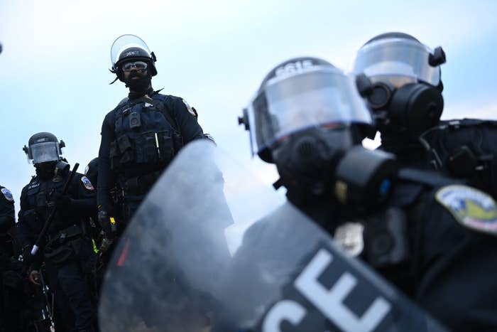 Officers wearing riot gear and face shields and carrying plastic shields