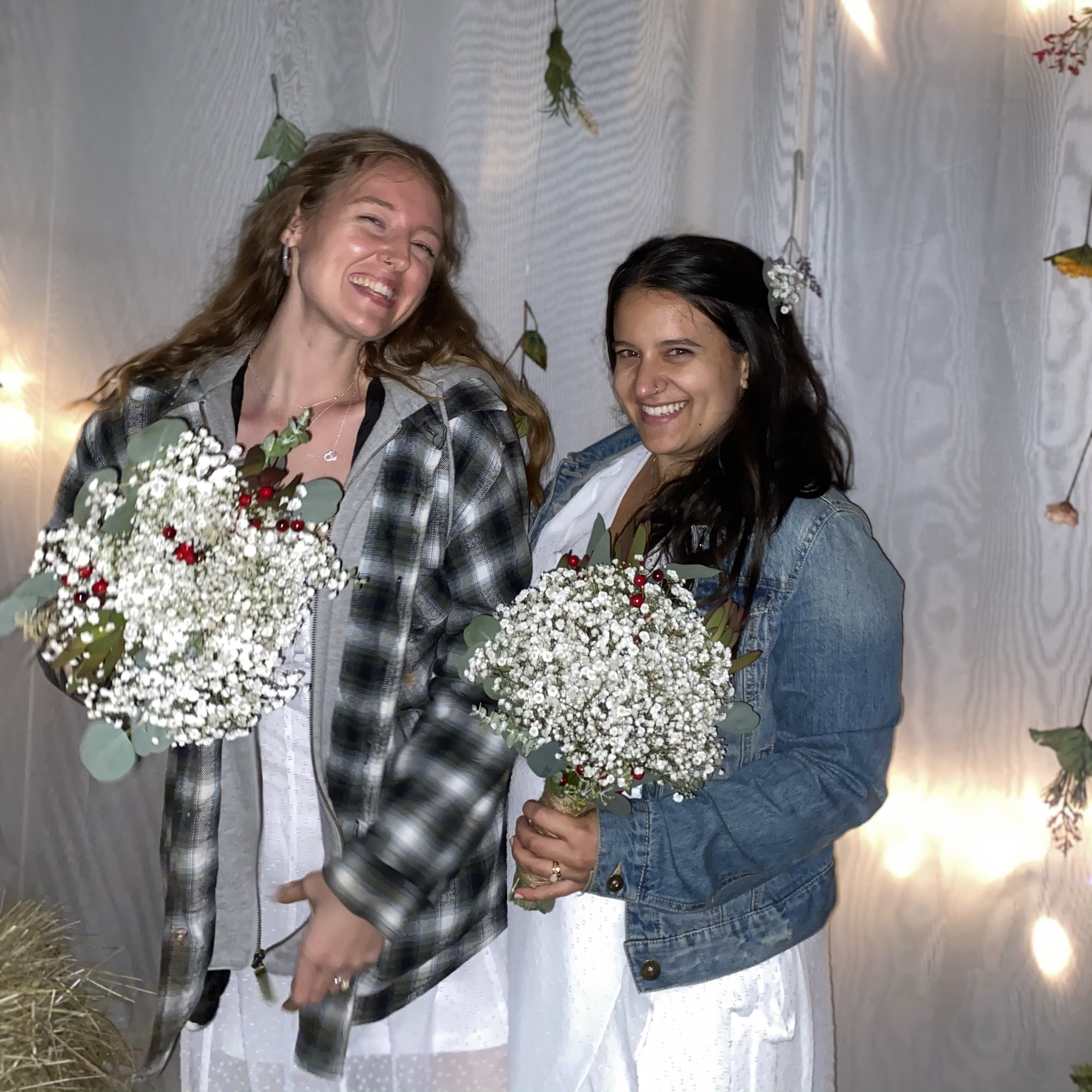 Marisa (left) and her wife (right) are grinning at the camera. They have jackets on over their wedding dresses, and are holding their bouquets.