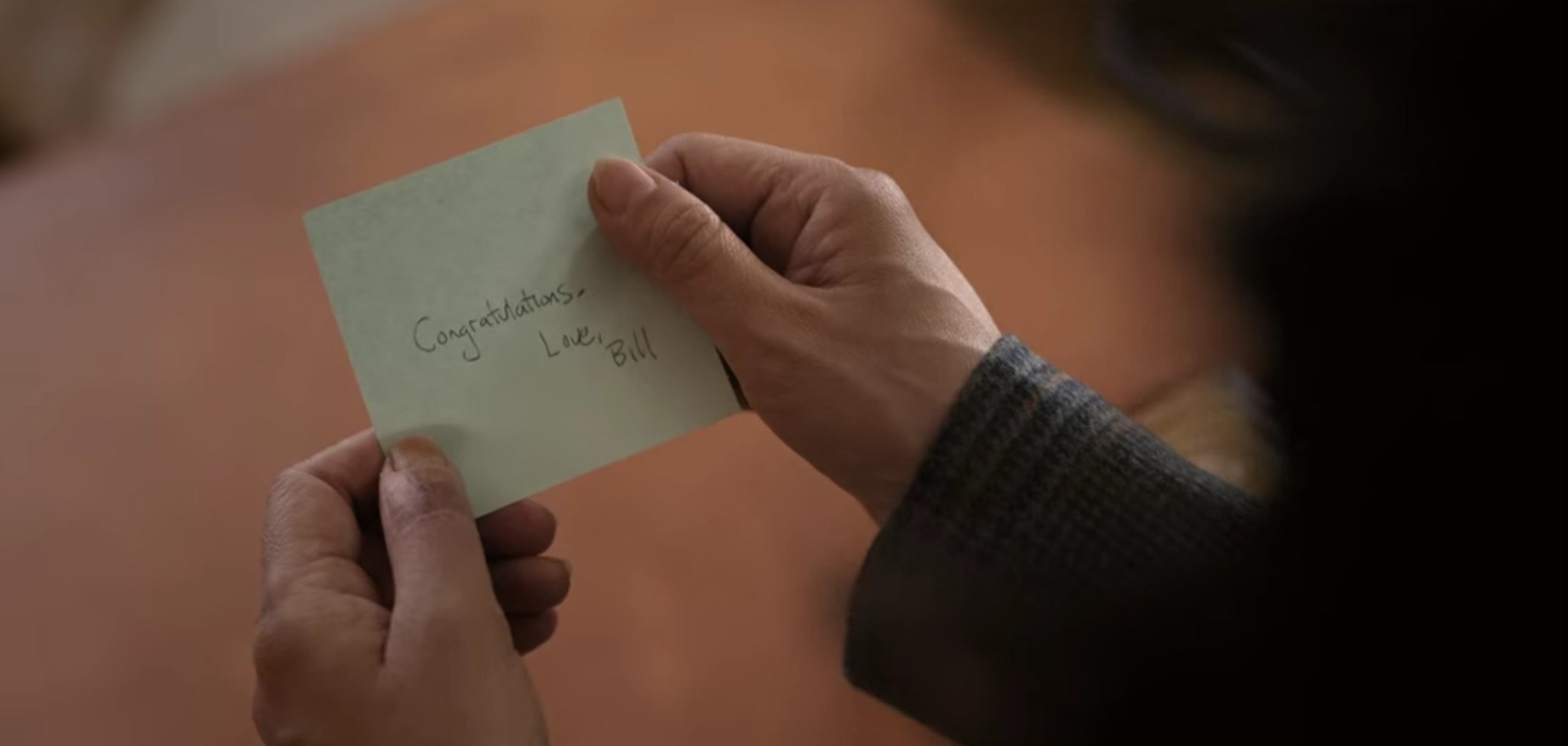 "Ji-Yoon reads note that says ""Congratulations. Love, Bill"""