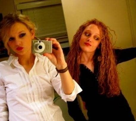 Taylor Swift taking a mirror selfie with a friend