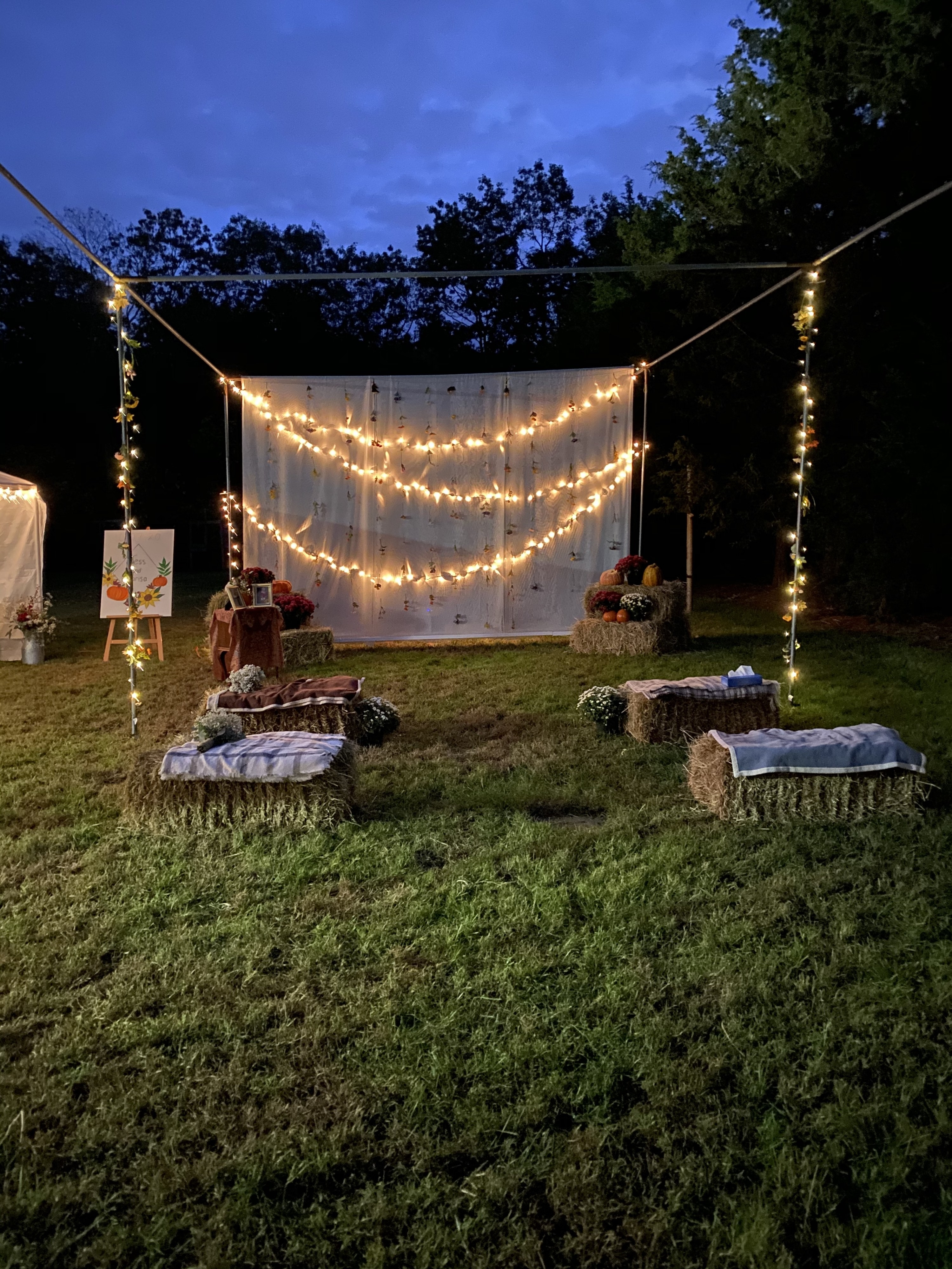 The frame of a batting cage is filled with hay bales with blankets, and decorated with string lights and a white backdrop.